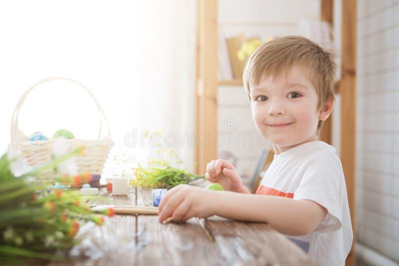Мальчик украшает пасхальное яйцо Картина мальчика и украшать пасхальные яйца Портрет милого мальчика 3 лет старого Он держит щетк стоковое фото rf