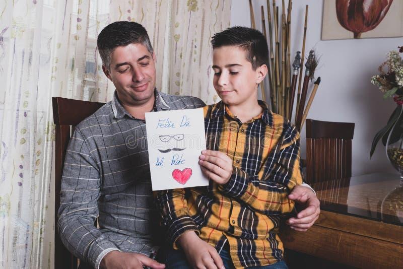 Мальчик читая поздравительную карту для того чтобы быть отцом на День отца стоковое изображение