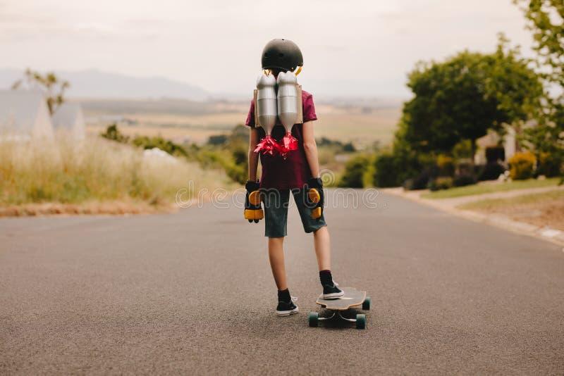 Мальчик Jetpack со скейтбордом стоковое изображение rf