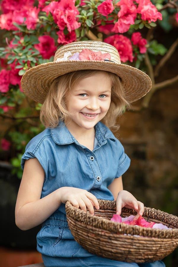 Малыш с корзиной цветка Девушка держа розовые цветки стоковое изображение