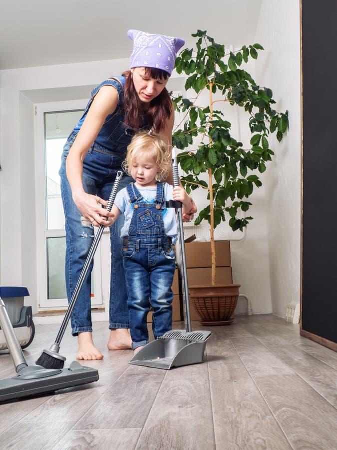 Мама и дочь в голубых прозодеждах джинсовой ткани очищают дом и стреловидность Мама учит, что дочь подметает стоковая фотография