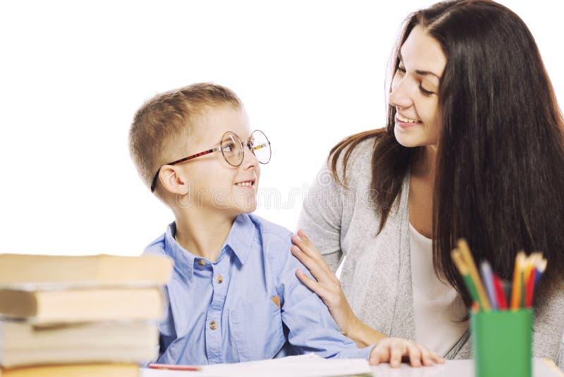 Мама помогает ее сыну сделать домашнюю работу, изолированную на белой предпосылке Нежность, влюбленность стоковое фото