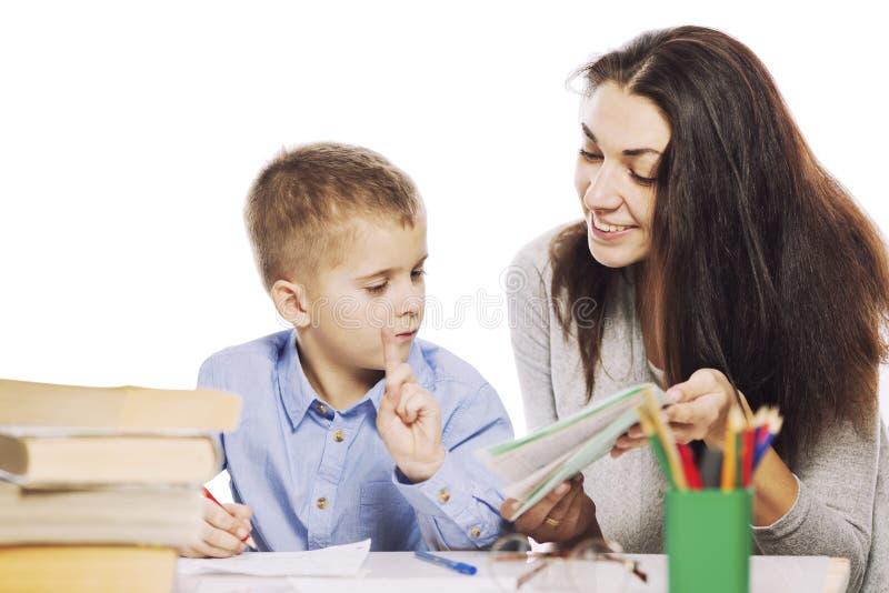 Мама помогает ее сыну сделать домашнюю работу, изолированную на белой предпосылке Нежность, влюбленность стоковая фотография rf