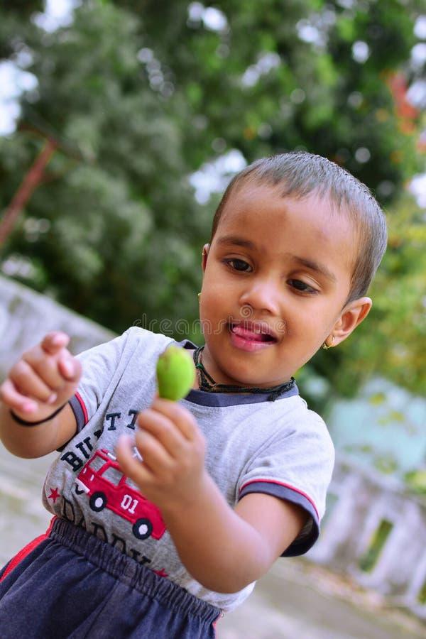 Манго зеленого цвета любов мальчика стоковые фотографии rf