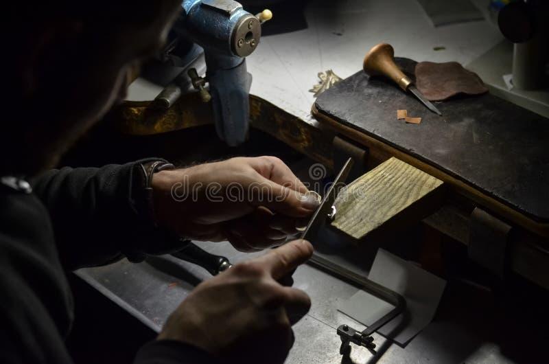 Мастерский ювелир держит инструмент работы в его руках и делает украшения на его рабочем месте в мастерской ювелирных изделий стоковая фотография
