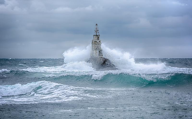 Маяк и шторм в море и больших волнах которое ломают в свет моря на порте Ahtopol, Чёрного моря, Болгарии стоковые фотографии rf