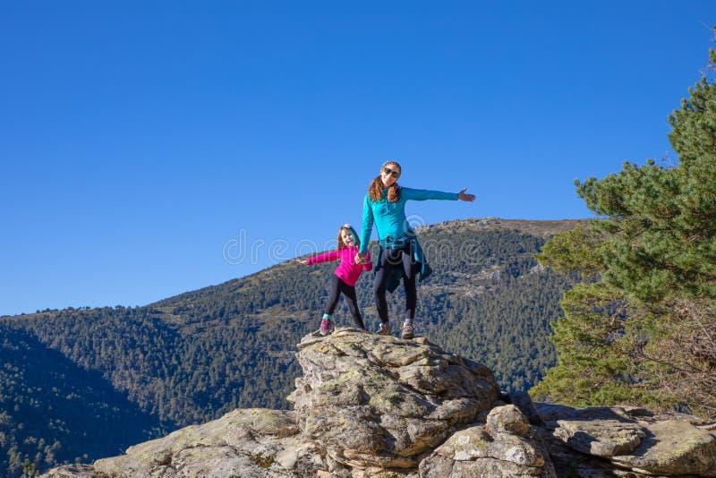 Мать альпиниста и ее маленькая дочь счастливые на верхней части горы стоковые изображения rf
