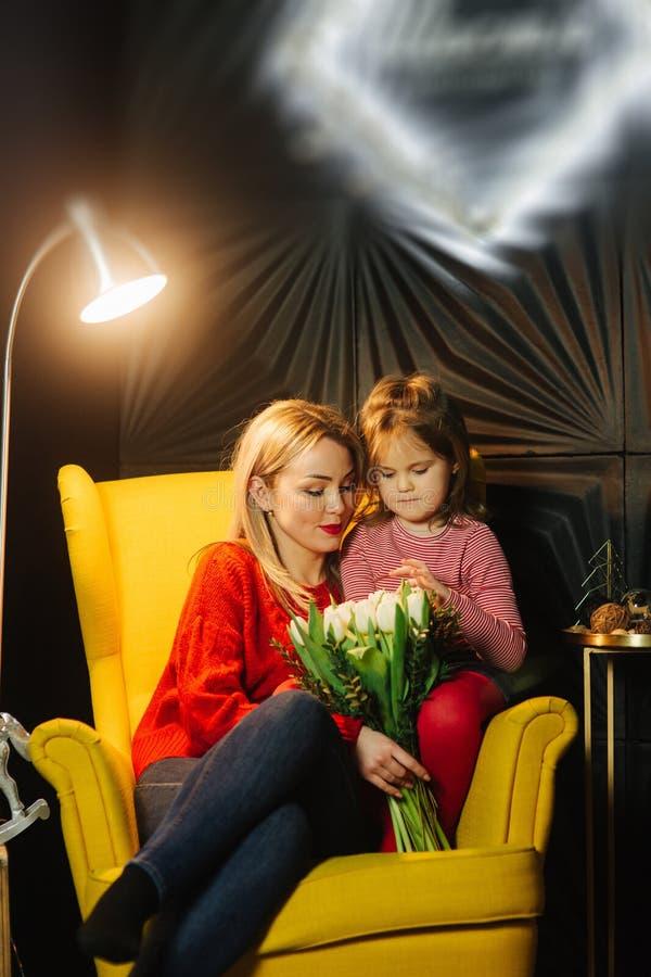 Мать и ее дочь сидя на желтом кресле и держа букет цветков стоковые фото