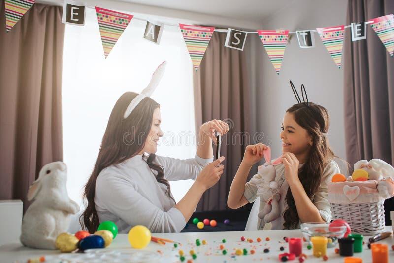 Мать и дочь подготавливают для пасхи Молодая женщина фотографирует девушка с игрушкой кролика Представление девушки Они носят пас стоковые фотографии rf