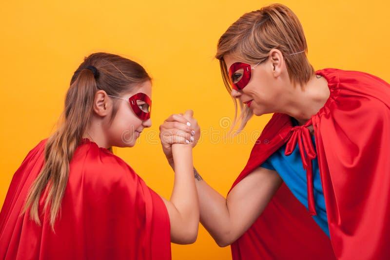 Мать и дочь одетые как супергерои играя армрестлинг над желтой предпосылкой стоковое изображение