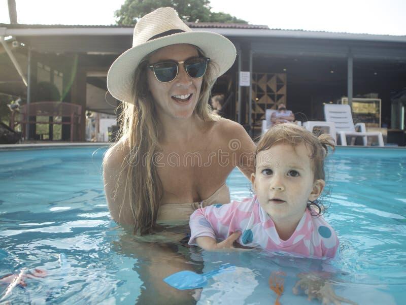 Мать наслаждаясь летним днем на бассейне с ее семьей стоковая фотография