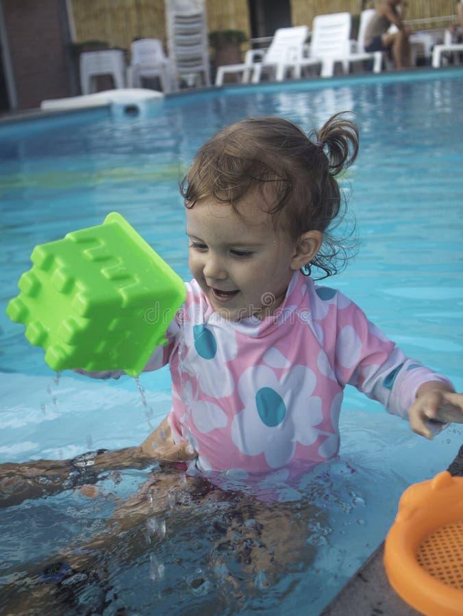 Мать наслаждаясь летним днем на бассейне с ее семьей стоковое изображение rf