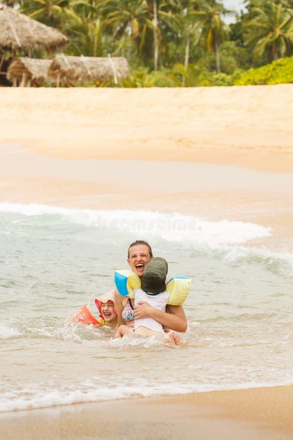 Мать наслаждаясь тропическим пляжем, играя в волнах с ее детьми стоковые фото