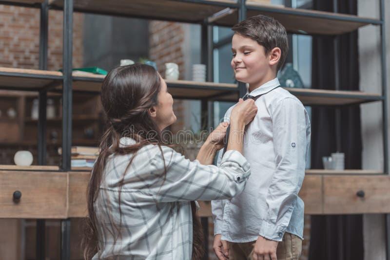 Мать помогая ее маленькому сыну получить одетый и связь стоковое фото rf