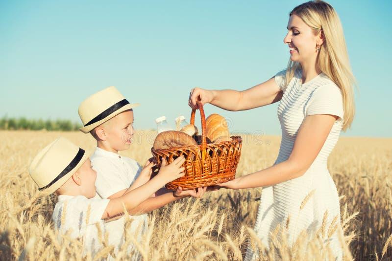 Мать дает детям корзину с свежим хлебом и молоком Пикник на пшеничном поле стоковые фотографии rf
