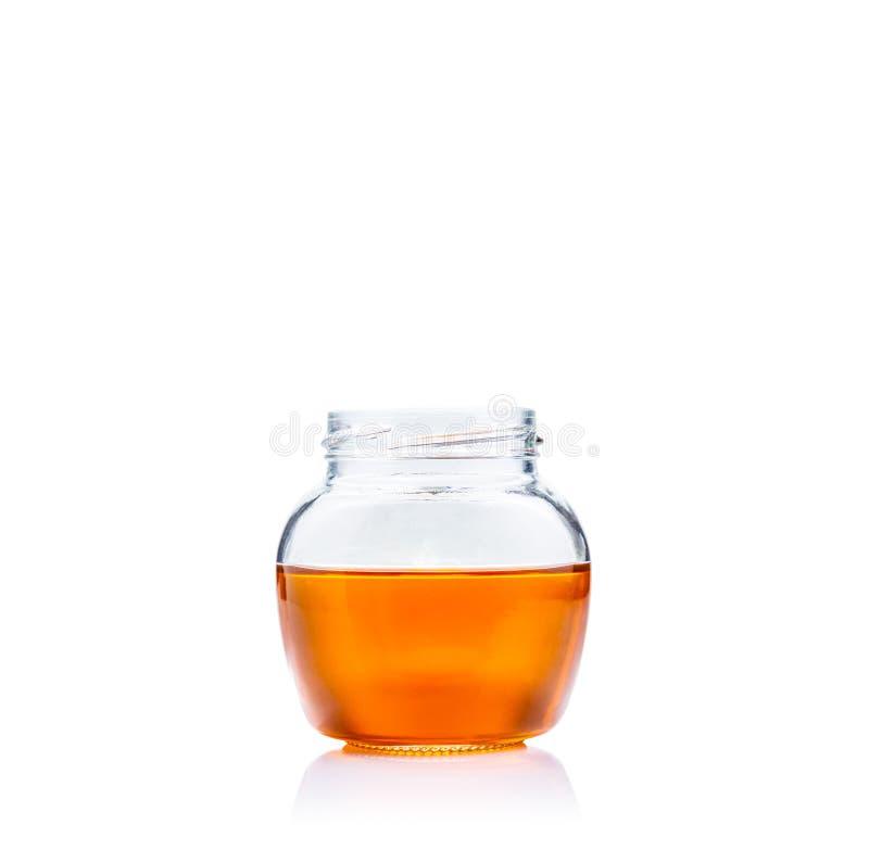 Мед в ясном стеклянном опарнике на белой предпосылке с космосом экземпляра стоковые изображения