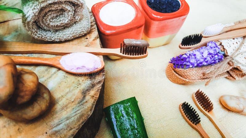 Место зубной щетки Eco дружелюбное естественное бамбуковое на деревянных плитах и зубной пасте сделанных из соли, угля и алоэ, ко стоковые изображения rf