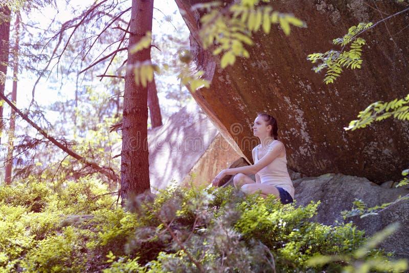 Мечтающ красивая девушка сидя на камне под утесом окруженным лесом на солнечный день стоковая фотография rf