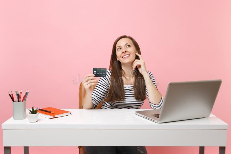 Мечтательная женщина держа кредитную карточку смотря вверх думающ как потратить деньги пока работающ усаживание на офисе с ноутбу стоковые изображения