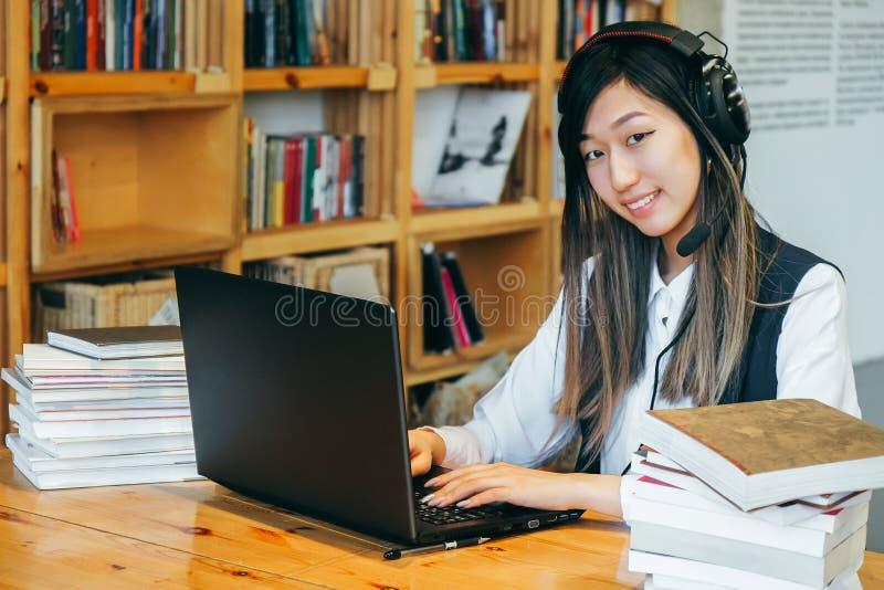 Милая азиатская девушка сидит в библиотеке в большом наушнике, окруженном книгами, работая на компьютере Студент подростка подгот стоковые фото