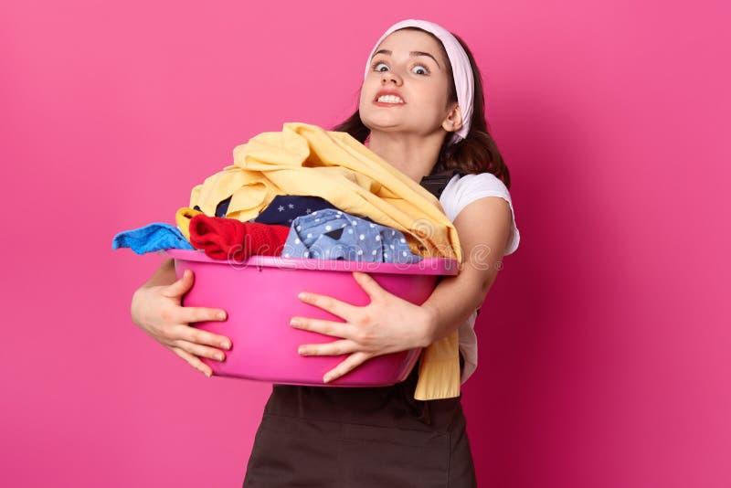 Милая женщина держит тяжелый таз с грязными одеждами, утомляла выражение лица, моет прачечную, одетую в коричневой изолированной  стоковое изображение rf
