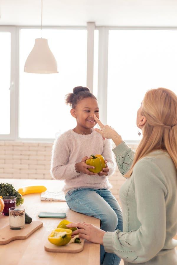 Милая жизнерадостная девушка держа перец пока помогающ варить матери стоковые фото