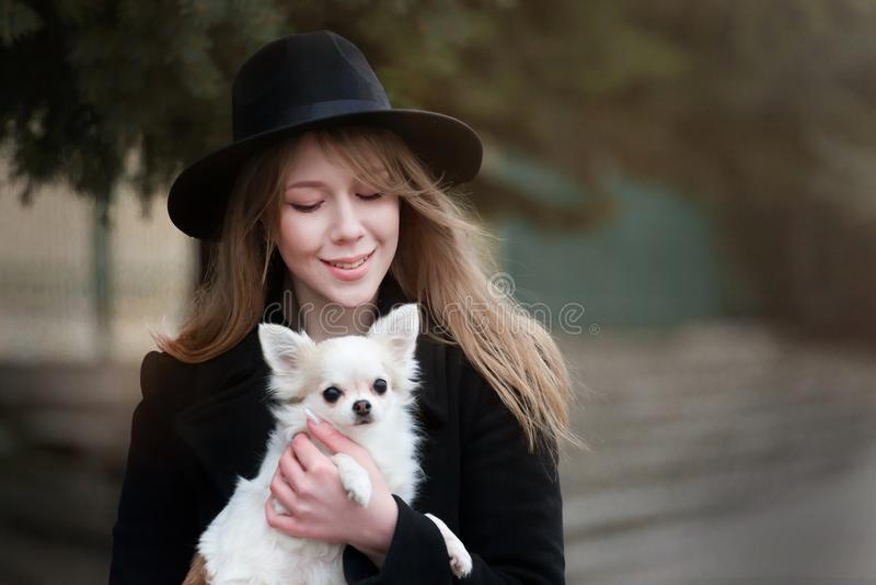 Милая жизнерадостная тонкая кавказская блондинка девушки с длинными волосами в черном пальто и черной шляпе внутри во дне осени с стоковые изображения