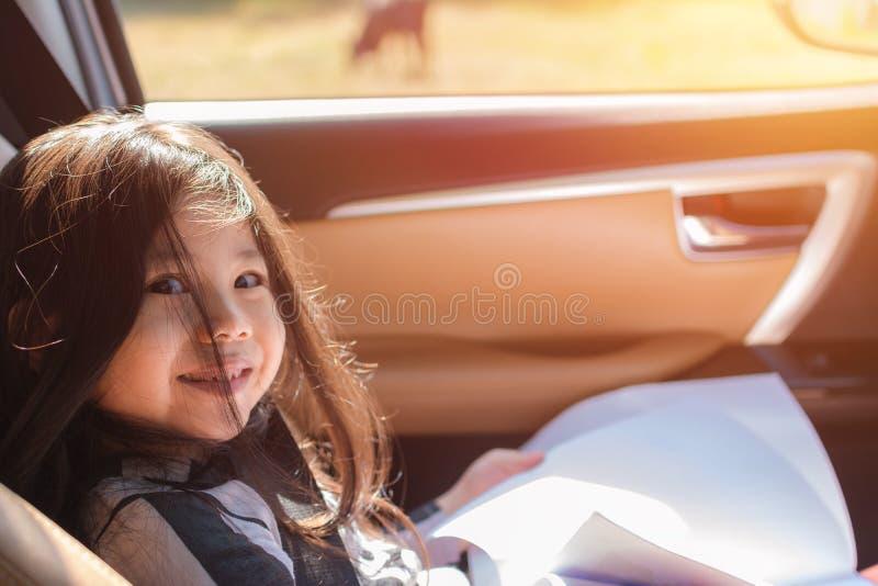 Милая маленькая азиатская девушка сидя на автомобиле стоковая фотография rf