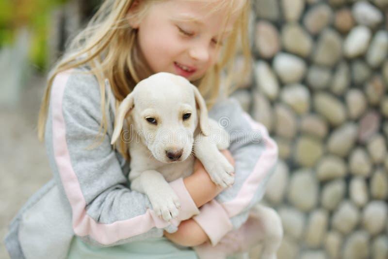 Милая маленькая девочка держа небольшого белого щенка outdoors Ребенк играя с собакой младенца на летний день стоковые фотографии rf
