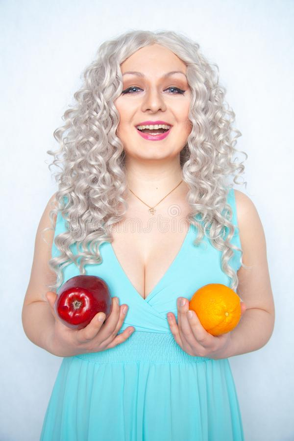 Милая маленькая девочка с курчавыми белыми волосами и пухлой диаграммой яблоком удерживания и оранжевым плодом на предпосылке сту стоковое фото