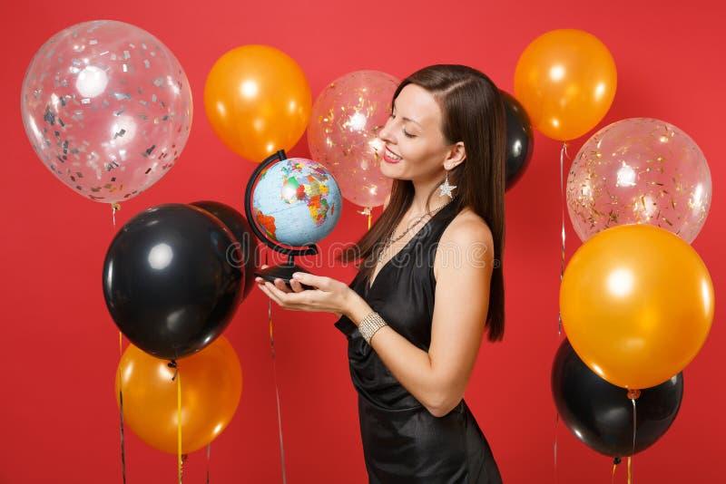Милая молодая женщина в меньший черный праздновать платья, смотря на глобусе мира в руках на красных воздушных шарах предпосылки стоковые фотографии rf