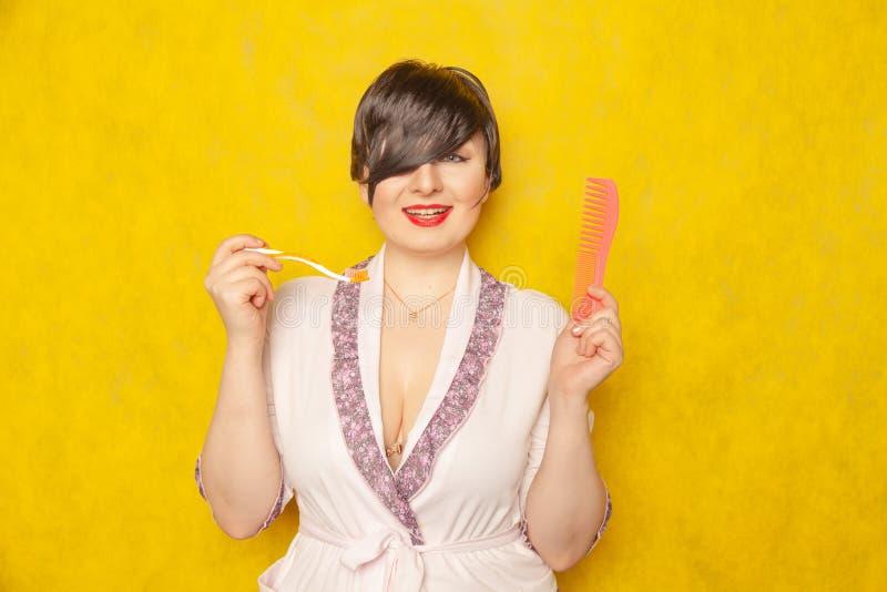 Милая пухлая девушка в розовой робе стоит с гребнем и зубной щеткой на желтой предпосылке в студии стоковое фото