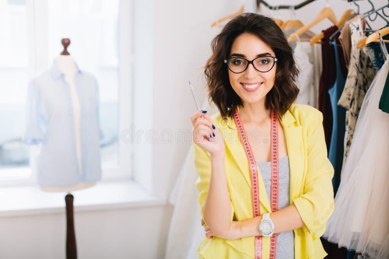 Милая девушка брюнета в сером платье и желтой куртке стоит около одежд в студии мастерской Она усмехаясь t стоковые изображения rf