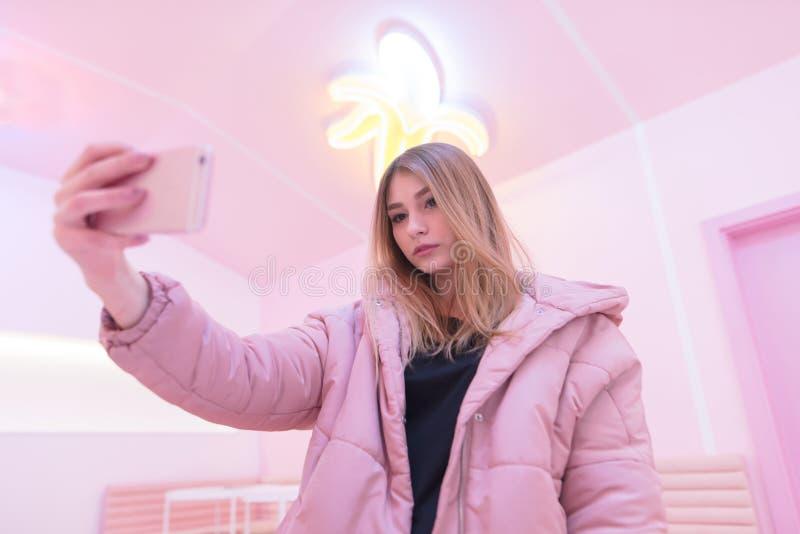 Милая девушка в пинке принимает snapphone sephi свой собственный на розовой внутренней предпосылке Розовая жизнь стоковая фотография rf