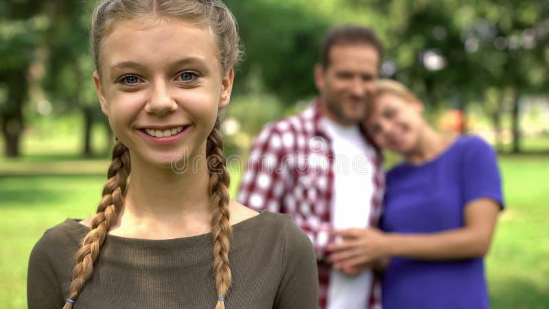 Милая девушка усмехаясь на предпосылке ее счастливой семьи родителей, любящих и заботить стоковые изображения