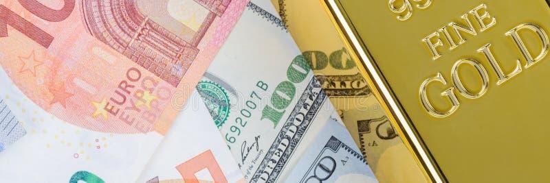 Миллиард слитка бара золота на фоне счетов доллара и евро стоковые изображения rf