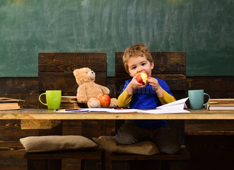 Милый зрачок порции учителя в классе на начальной школе Студенты могут получить обучение в почти каждом вопросе стоковое изображение rf