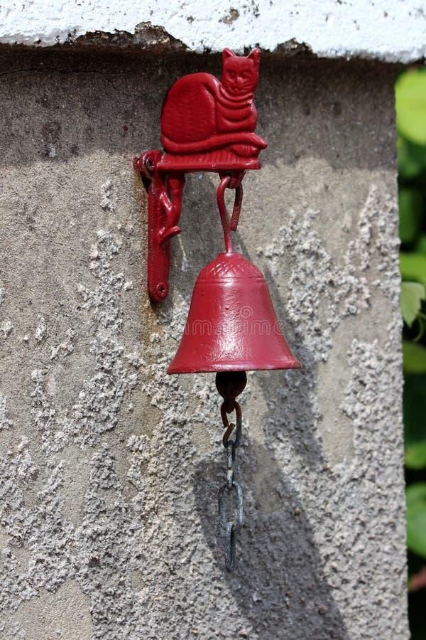 Милый красный кот металла и украшение колокола используемое как дверной звонок установленный на стороне стены дома на входе задво стоковая фотография rf