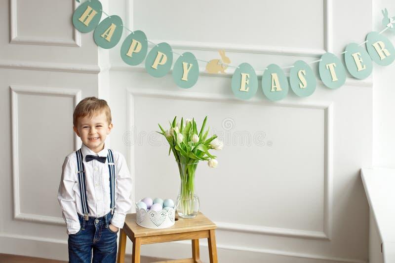 Милый мальчик в белых рубашке и бабочке стоит в светлой комнате около деревянного стола со стеклянной вазой тюльпанов и a стоковое изображение