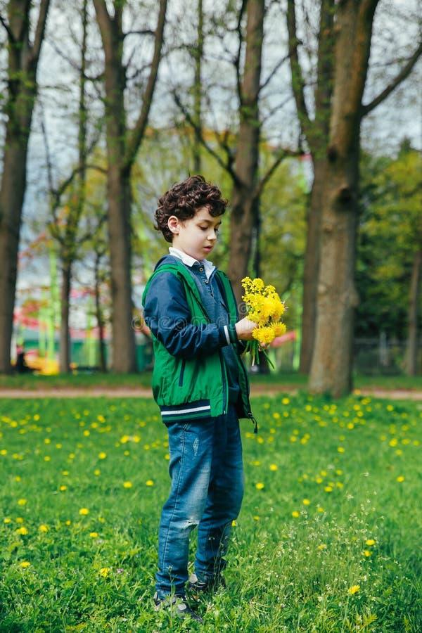 Милый мальчик с одуванчиками в парке на теплый весенний день, стоковое фото rf