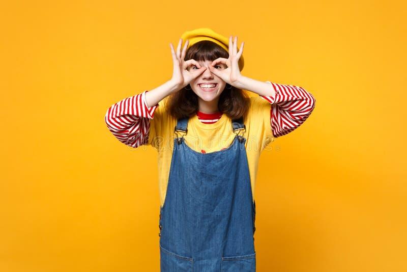 Милый подросток девушки во французском берете, sundress джинсовой ткани держа руки около глаз имитируя стекла или бинокли изолиро стоковое изображение rf
