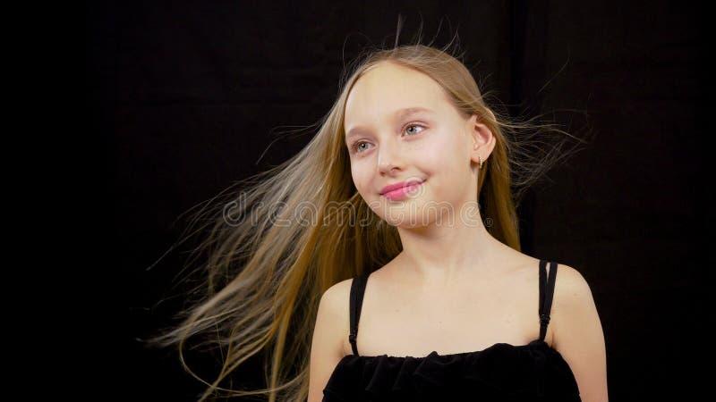 Милый подросток девушки с развевая волосами на ветре представляя на черной предпосылке в студии стоковое фото