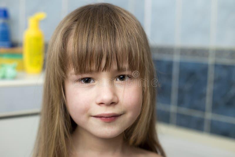 Милый портрет стороны девушки, усмехаясь ребенок с красивыми глазами и длинные влажные справедливые волосы на запачканной предпос стоковые фотографии rf