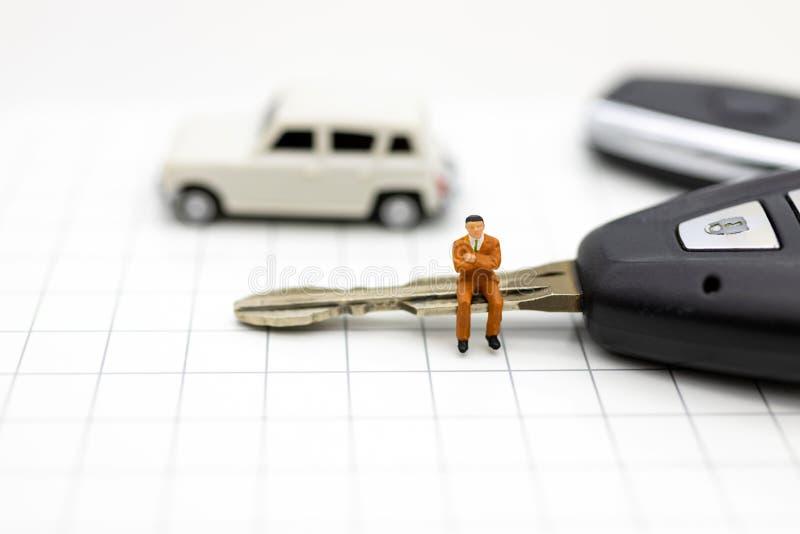 Миниатюрные люди: Бизнесмен сидя на ключе автомобиля Польза изображения для рекламировать продукт в рынке сегодня, конкуренция на стоковые изображения rf