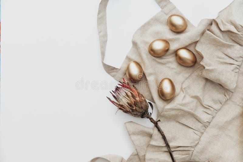 Минимальные плоские положенные пасхальные яйца золота с рисбермой белья и цветком protea на белой предпосылке стоковое изображение