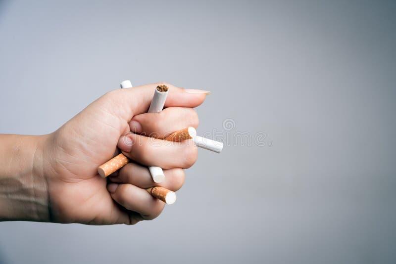 Мир отсутствие дня табака, 31-ое мая куря стоп Сигареты близкой поднимающей вверх руки человека задавливая и разрушая на серой пр стоковое изображение