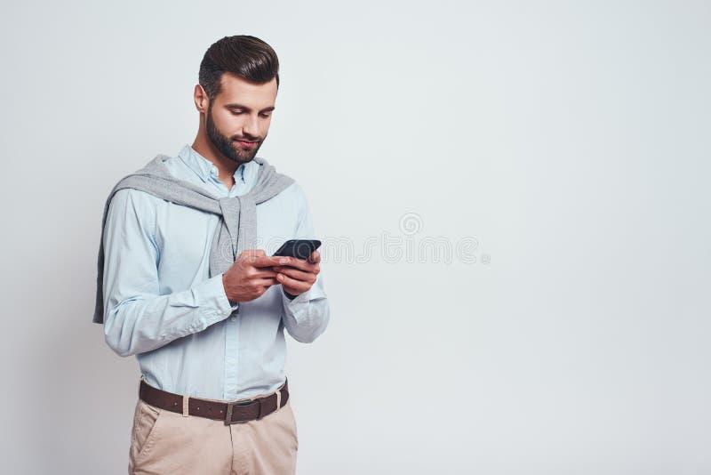 многодельно очень Красивый молодой человек в случайной носке используя его умный телефон пока стоящ на серой предпосылке Концепци стоковые изображения