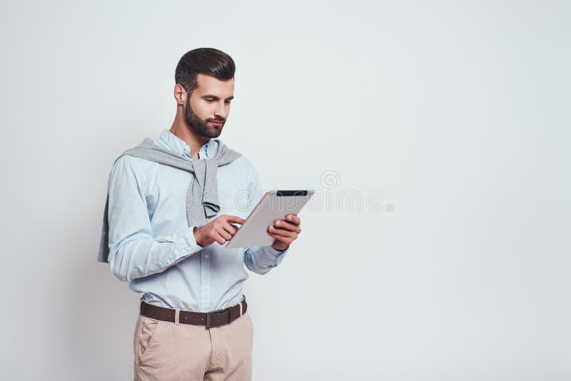 многодельно очень Стильный бородатый человек в случайной носке использует его цифровой планшет для работы пока стоящ на серой пре стоковые изображения rf
