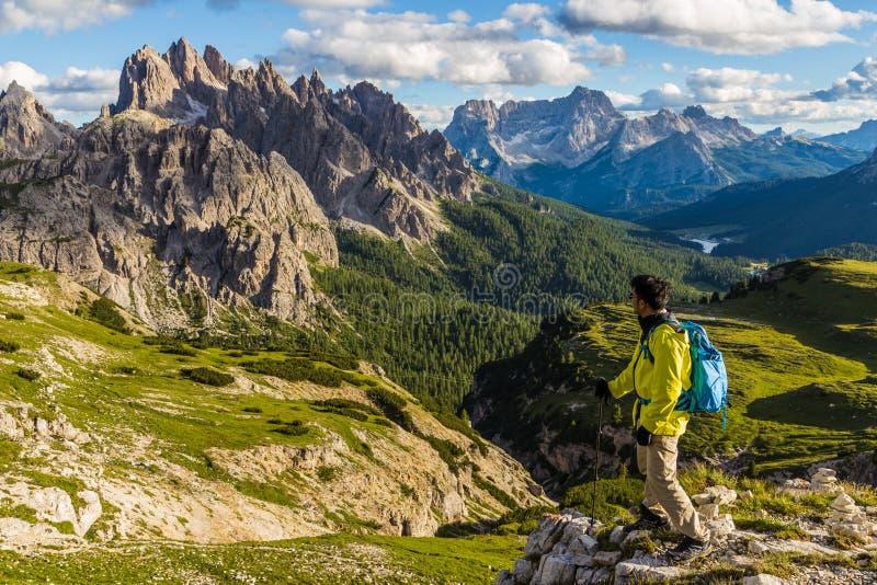 Мужской азиатский hiker смотря величественный взгляд ряда moutain доломитов в следе Tre Cime di Lavaredo стоковые изображения