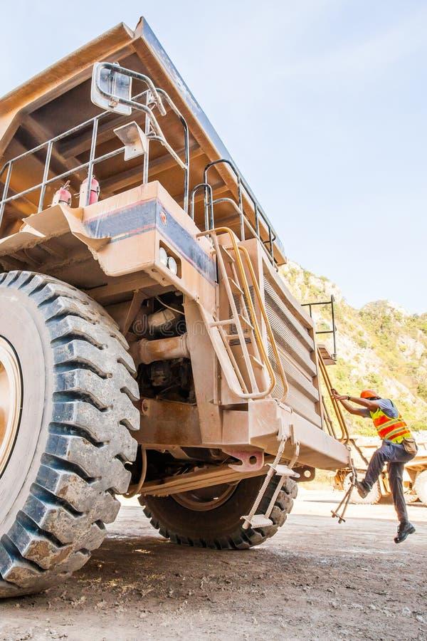 Мужской водитель идет вверх по лестницам большого самосвала карьера, минералам продукции полезным, для того чтобы транспортироват стоковые фотографии rf